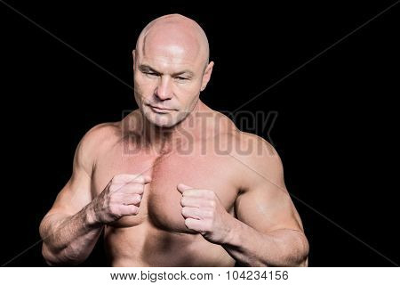 Bald man in boxing pose against black background