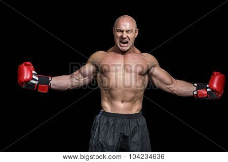 Successful boxer with arms outstretched against black background