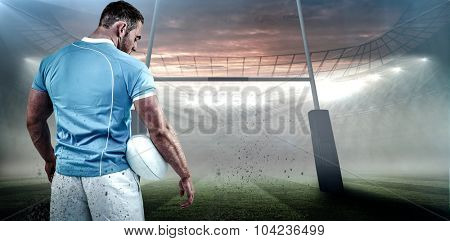 Rugby player standing with ball against rugby stadium