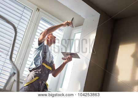 Thirty years old manual worker with wall plastering tools inside a house. Plasterer renovating indoor walls and ceilings with float and plaster. poster