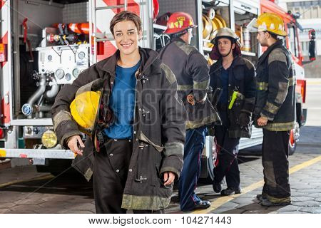 Portrait of happy firewoman with male colleagues discussing by truck in background at fire station