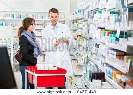 Smiling male pharmacist showing medicine to female customer in pharmacy