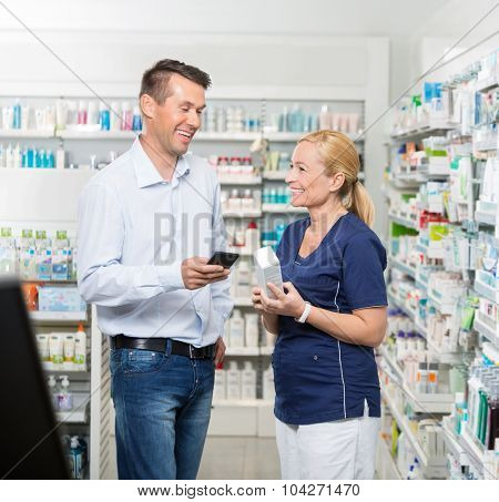 Happy mid adult male customer holding mobile phone while pharmacist showing product in pharmacy