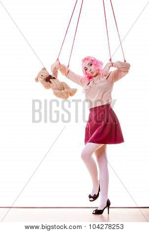 Mental disorder concept. Young woman girl stylized like marionette puppet on string with teddy bear toy isolated on white background poster