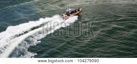ORLANDO, FLORIDA - SEPTEMBER 26, 2015: A US Coast Guard 25 Foot Defender Class Boat Patrols the departure of a Cruise Ship into the open seas Orlando, Florida on September 26, 2015.