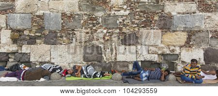 KOS, GREECE - SEP 27, 2015: Refugees sleeping on the ground along the stone wall. Kos island is located just 4 km. from the Turkish coast, and many refugees come from Turkey in an inflatable boats.