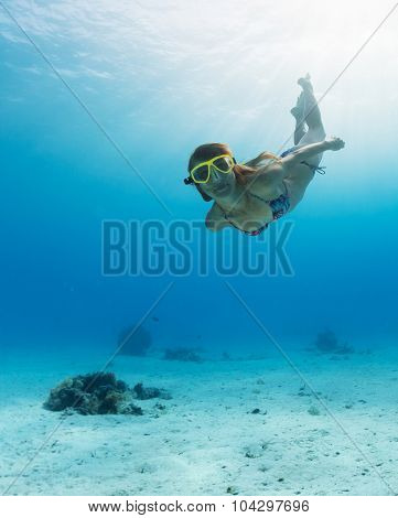 Underwater shot of the young lady skin diving in the clear tropical sea