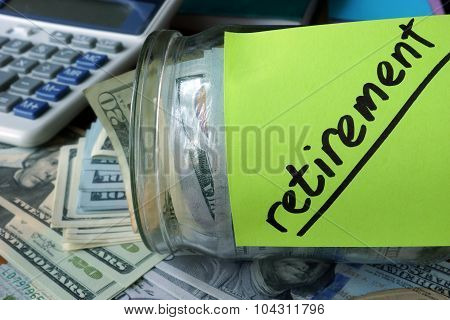 Jar with label Retirement Plan and money on the table.
