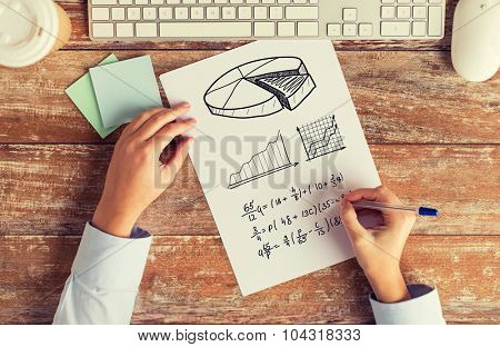 business, education, technology and people concept - close up of female hands with pencil and computer keyboard solving task or writing mathematical equation to notebook