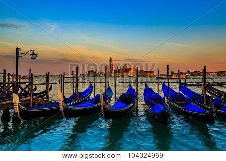 Gondolas in Venice - sunset with San Giorgio Maggiore church. San Marco, Venice, Italy. (filtered, intentional motion blur).
