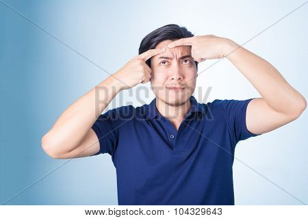 Handsome Asian man Squeezing pimple acne on blue background poster