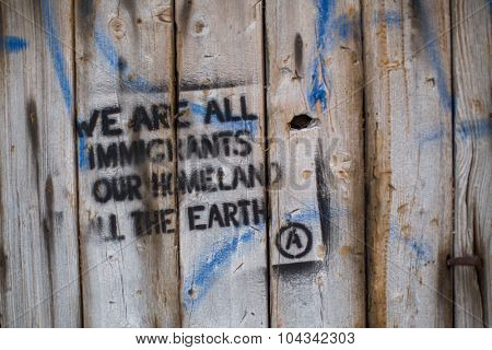 KOS, GREECE - SEP 28, 2015: Stencil on the wall: We are all immigrants, our homeland all the earth. Kos is located just 4 km from the Turkish coast, and many refugees come from Turkey in an boats.