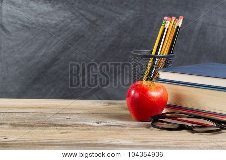 Old Wooden Desktop With Reading Materials And Blackboard