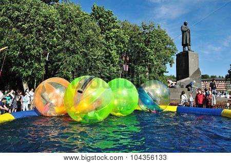 VELIKY NOVGOROD RUSSIA - 12 JUNE 2015. Unidentified kids zorb inside large balls on water during the City Day in Veliky Novgorod