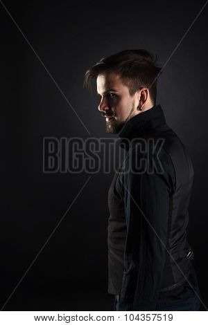 handsome brutal guy with beard on dark background in studio poster