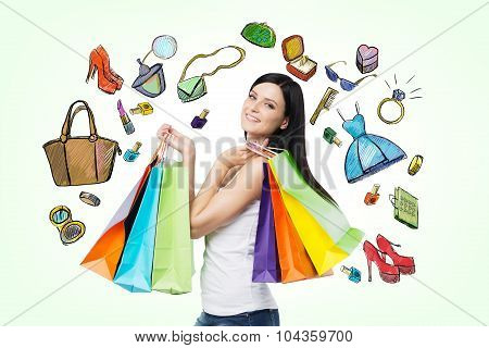 Beautiful Smiling Young Woman With The Colourful Shopping Bags From The Fancy Shops. Light Green Bac