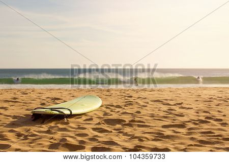 Surf Board In The Sand On The Beach At Sunset