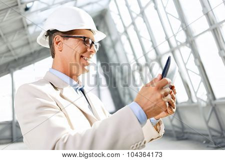 Pleasant architect holding laptop
