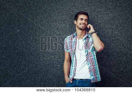 Young Man Talking On The Smart Phone Leaning Against A Gray Wall