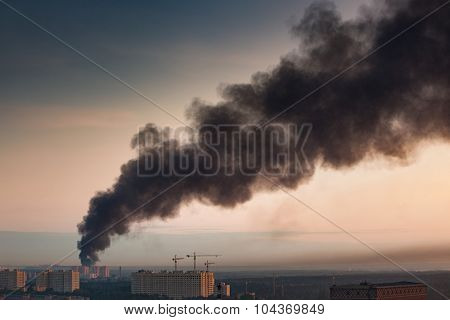 Smoke at sky of morning city. Big fire at apartment house. Warm sunrise colors. poster