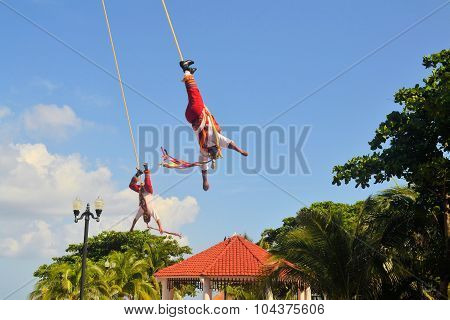 Playa del Carmen, Riviera Maya, Yucatan, Mexico - 19 August 2013: Acrobat performers, so-called Voladores, perform a Flying Men Dance ceremony near the beach of Playa del Carmen. The fertility ritual is a traditional Ceremony of Mayans and other tribes.