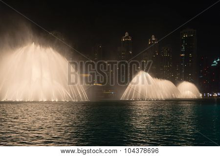 Lighted Fountains Performing Dramatic Effects Along Urban Beachfront At Night