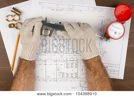 Mans hands in gloves holding trammel and pencil