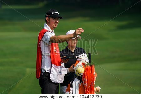 KUALA LUMPUR, MALAYSIA - OCTOBER 09, 2015: South Korea's Eun-Hee Ji discusses with her caddy on the 6th hole fairway of the KL Golf & Country Club at the 2015 Sime Darby LPGA Malaysia golf tournament.