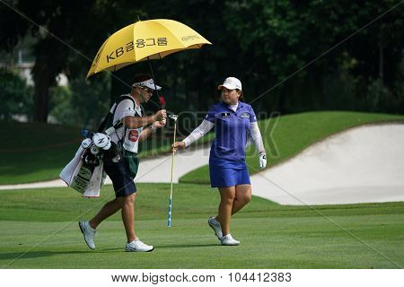 KUALA LUMPUR, MALAYSIA - OCTOBER 09, 2015: South Korea's Inbee Park passes the club to her caddy on the fairway of the KL Golf & Country Club at the 2015 Sime Darby LPGA Malaysia golf tournament.