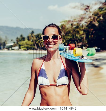 Beautiful sexy lady in blue and white striped bikini with penny longboard and sunglasses walks along the water line poster