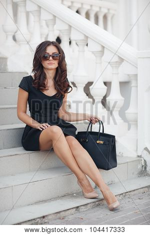 Portrait of the woman sitting on steps with a white handrail