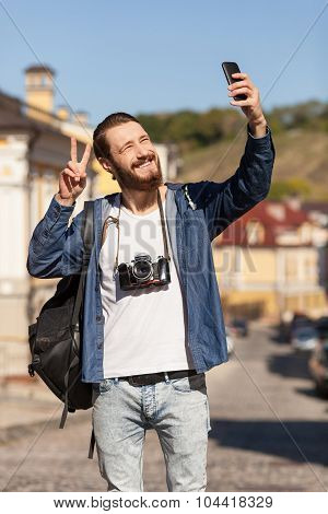 Attractive bearded man is photographing during travel