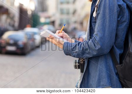 Young male explorer is noting something in city