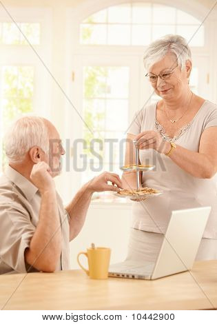 Smiling Wife Serving Cookies In Kitchen To Husband