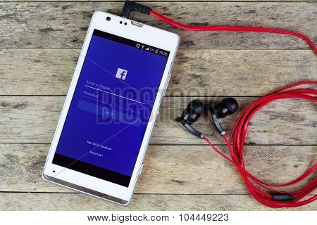 Bung Kan, Thailand - September 02, 2015: Using Facebook By Smart Phone With Earphones