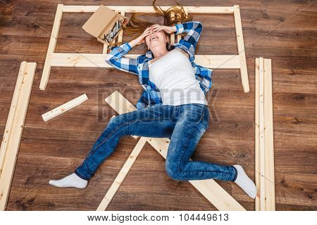 Happy woman having fun assembling furniture at home. Young girl laying on floor arranging apartment house interior. DIY. High angle view. poster