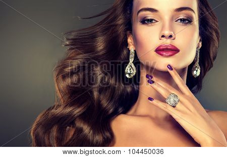Beautiful model brunette with long curled hair. Violet manicured nails  ,   jewelry earrings   and r
