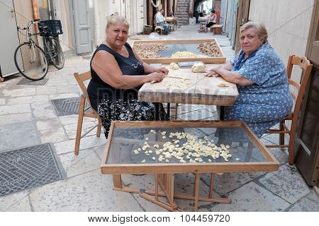 OLD BARI, ITALY - JULY 06: mother and daughter working the dough to make fresh pasta in the street Arco Basso of Old Bari, also known as the street of