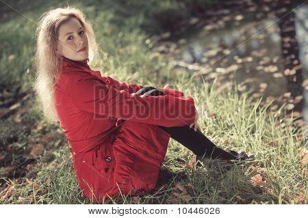 Young Woman Sitting On Lake Bank