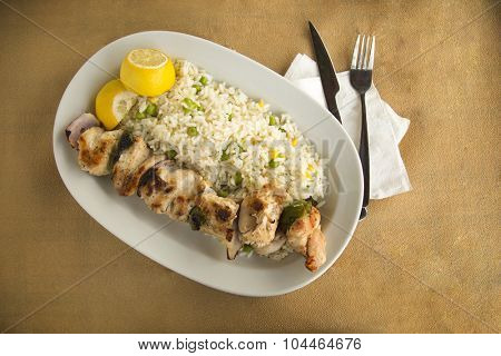 Chicken souvlaki with white rice with peas served with fresh lemon