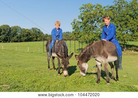 Farm boys riding on their donkeys