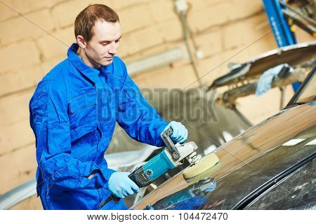 mechanic polishing car body at automobile repair and renew service station shop by power buffer machine