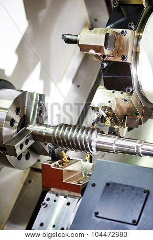 metalworking  industry. cutting tool processing steel metal spiral pinion or worm screw shaft on lathe machine in workshop. Focus on tool. poster