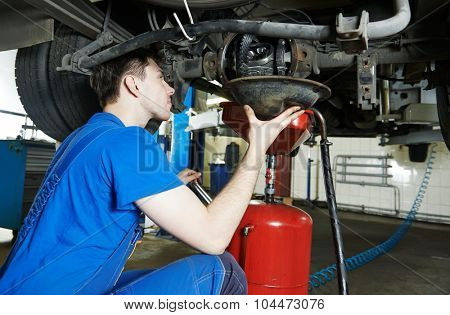 auto repairman mechanic works with rear axle reduction gear of commercial van in car auto repair or maintenance shop service station