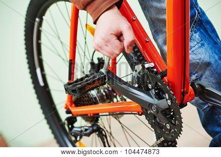 Bike maintenance: mechanic serviceman repairman installing assembling or adjusting bicycle gear on wheel in workshop