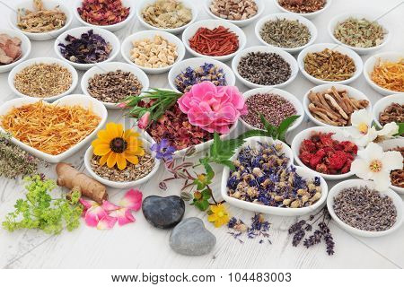 Large herb and flower selection used in herbal medicine in porcelain bowls over distressed wooden background.