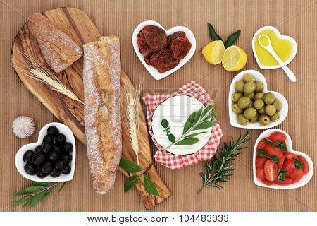 Picnic food with french baguette loaf on an olive wood board, camembert cheese, olives, sun dried and fresh tomatoes, oil, lemon, garlic and herb leaf sprigs. poster