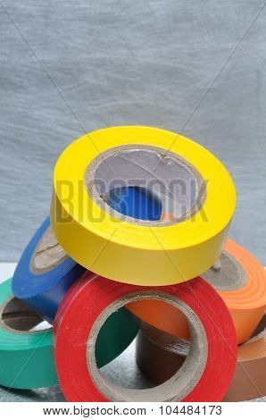 Set of multicolored insulating tapes on metal grey background poster