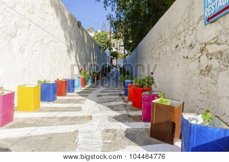 A typical greek island cobbled alley in Chora Mykonos Greece decorated with colourful flower pots of geranium and surrounded by whitewashed architecture. poster
