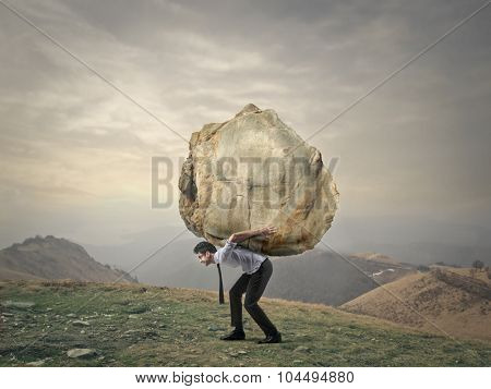 Businessman carrying a big rock
